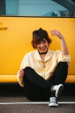 portrait of young asian woman sitting with yellow background